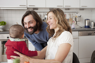 Happy parents with baby girl in kitchen - FSIF00062