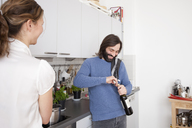 Woman looking at smiling man opening wine bottle in kitchen - FSIF00077