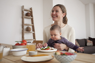 Happy woman looking away while sitting with baby girl at home - FSIF00080