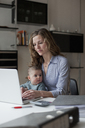 Woman using laptop while sitting with baby girl at home - FSIF00083