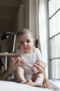 Cute baby girl sitting on father at home - FSIF00089