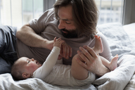 Affectionate father with baby girl in bedroom - FSIF00092