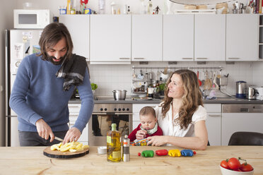 Father chopping vegetables with woman and baby girl sitting in kitchen - FSIF00107