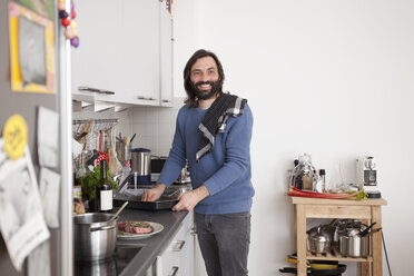 Smiling man looking away while preparing food in domestic kitchen - FSIF00110