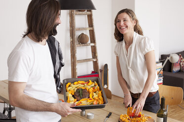 Smiling couple preparing pumpkin dish at home - FSIF00113
