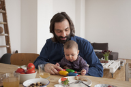 Father with baby girl playing with toy at table - FSIF00116