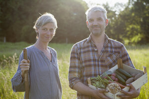 Portrait of mature couple with crate of freshly harvested vegetables at garden - FSIF00176