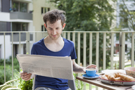 Young man reading newspaper while having breakfast at porch - FSIF00191