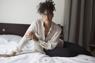 Thoughtful woman with curly hair sitting on bed at home - FSIF00194