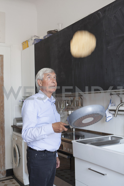 Senior man tossing pancake on frying pan in kitchen at home - FSIF00269 - fStop/Westend61