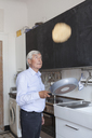 Senior man tossing pancake on frying pan in kitchen at home - FSIF00269