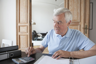 Senior man using calculator to calculate home finances at table - FSIF00272