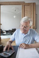 Senior man calculating home finances at table - FSIF00275