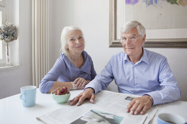 Portrait of happy senior couple sitting with newspaper at table - FSIF00278