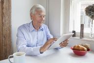 Senior man using digital tablet at breakfast table - FSIF00281