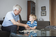 Happy grandson and grandfather looking at each other while solving jigsaw puzzle in living room - FSIF00284