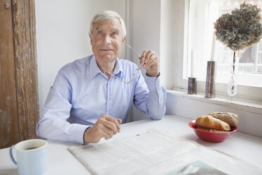 Thoughtful senior man looking away while holding glasses at breakfast table - FSIF00287