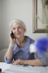 Smiling senior woman answering mobile phone at table - FSIF00290