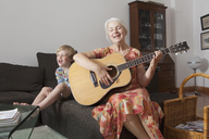 Playful boy sitting with grandmother singing while playing guitar on sofa at home - FSIF00293