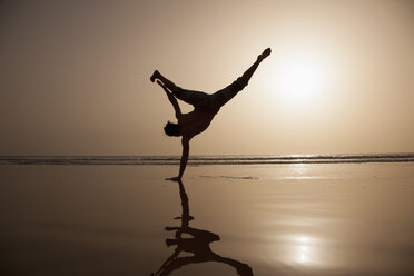 Full length of silhouette man performing handstand at beach - FSIF00308