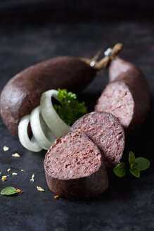Sliced blood sausages, onion rings, parsley and herbs on dark ground - CSF28905
