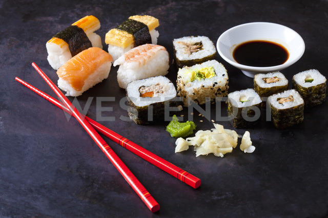 Variety of sushi with wasabi, ginger and bowl of soy sauce on dark ground - CSF28917
