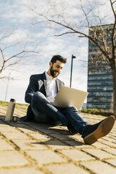 Businessman using laptop outside office building - JRFF01537