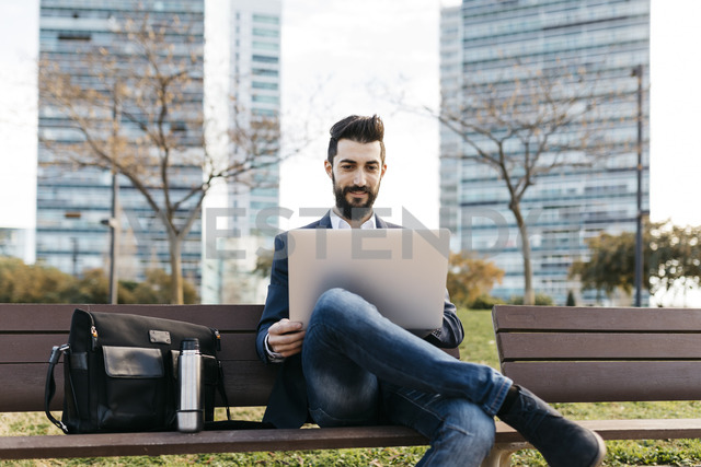 Businessman sitting on bench outside office building using laptop - JRFF01540