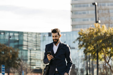 Businessman using cell phone outside office building - JRFF01543