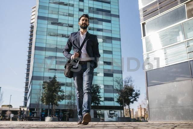 Businessman walking outside office building - JRFF01546