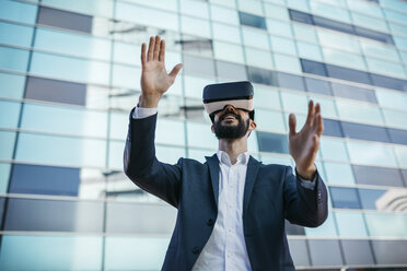 Businessman using virtual reality glasses outside office building - JRFF01549