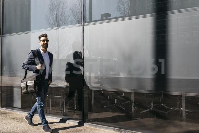Businessman wearing sunglasses walking along building - JRFF01552