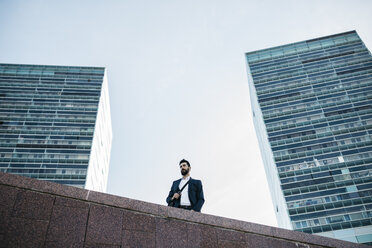 Businessman standing in front of office towers - JRFF01555