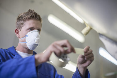 Worker in a factory wearing dust mask taping - ZEF14951