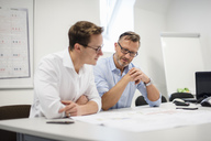 Two businessmen discussing plan on desk in office - DIGF03297