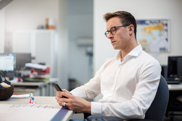 Young businessman using cell phone at desk in office - DIGF03315