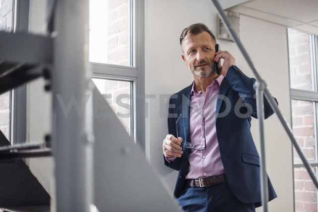 Mature businessman on cell phone at the window - DIGF03318