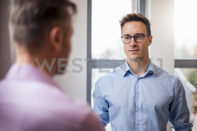 Two businessmen talking at the window - DIGF03324