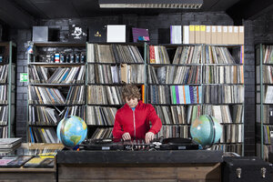 A young man using a sound mixer and DJ decks at a record store - FSIF00356