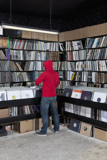 A young man looking through records at a record store, rear view - FSIF00359