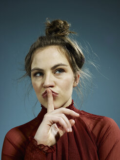 A young hip woman with her index finger on her lips, thinking - FSIF00386