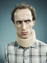A displeased man wearing a neck brace and looking suspiciously to the side - FSIF00392