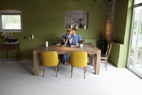 An affectionate couple sitting at a table with a personal organizer and coffee - FSIF00437