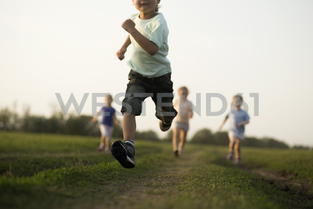Low view of a boy running in a field with other children behind - FSIF00458 - fStop/Westend61