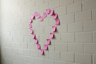 Blank adhesive notes arranged into the shape of a heart on a brick wall - FSIF00464