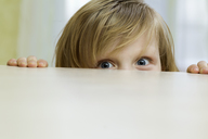 A mischievous girl peeking over the top of a table - FSIF00467