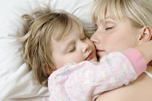 A mother and her young daughter sleeping a bed side by side - FSIF00476