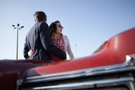 A cool, rockabilly couple with arms around each other by a vintage car - FSIF00488