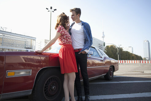 A flirtatious rockabilly couple standing next to a vintage car, Berlin, Germany - FSIF00491