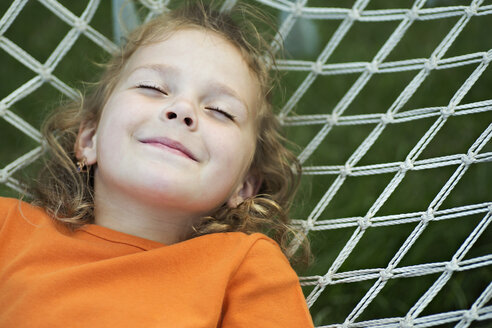 A young smiling girl lying on a hammock with her eyes closed - FSIF00518